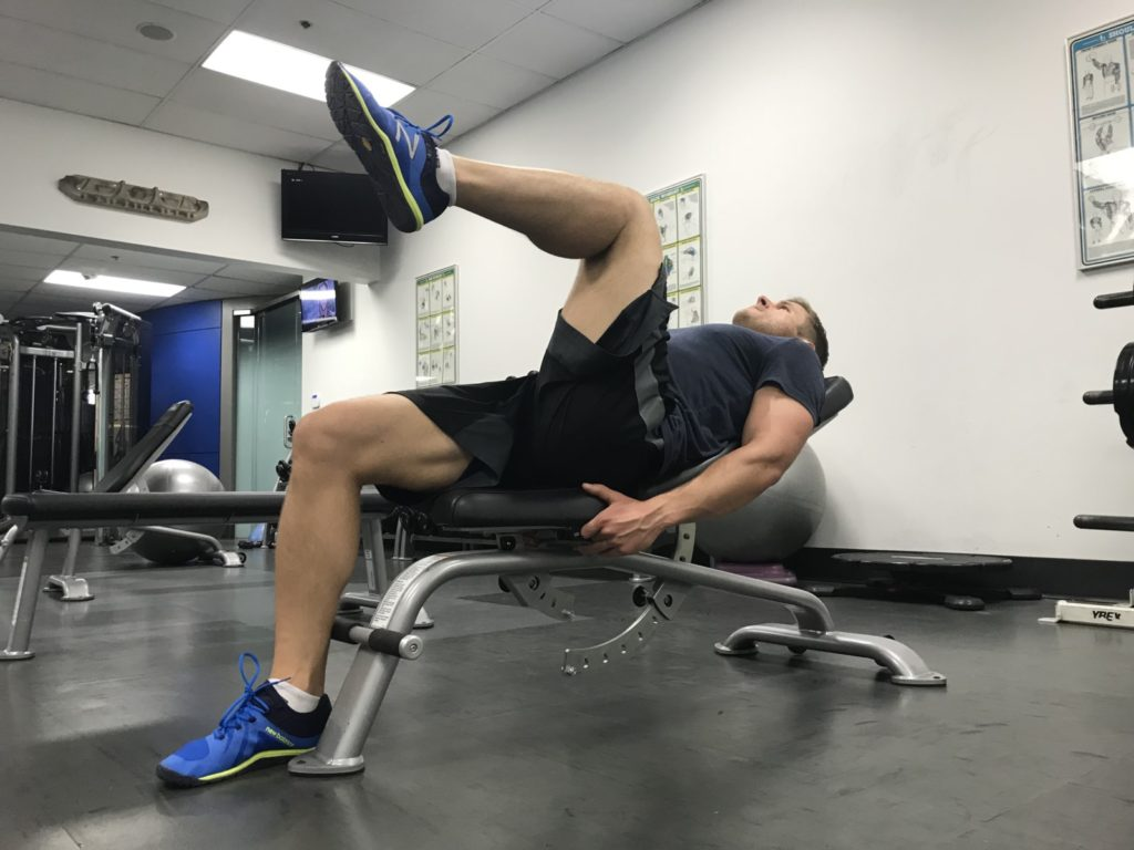 Hip flexion exercise on an incline bench